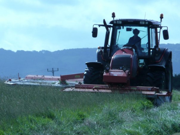 Red tractor mowing